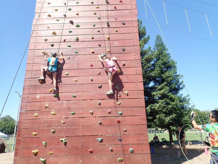 Kids rock climbing at summer camp at ropes course