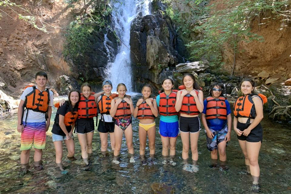 Youth in front of waterfall in the outdoors on a hike at summer camp